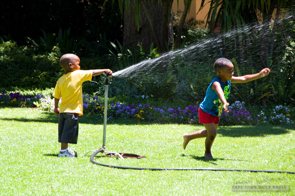 A kid, a sprinkler, and a really wet sibling