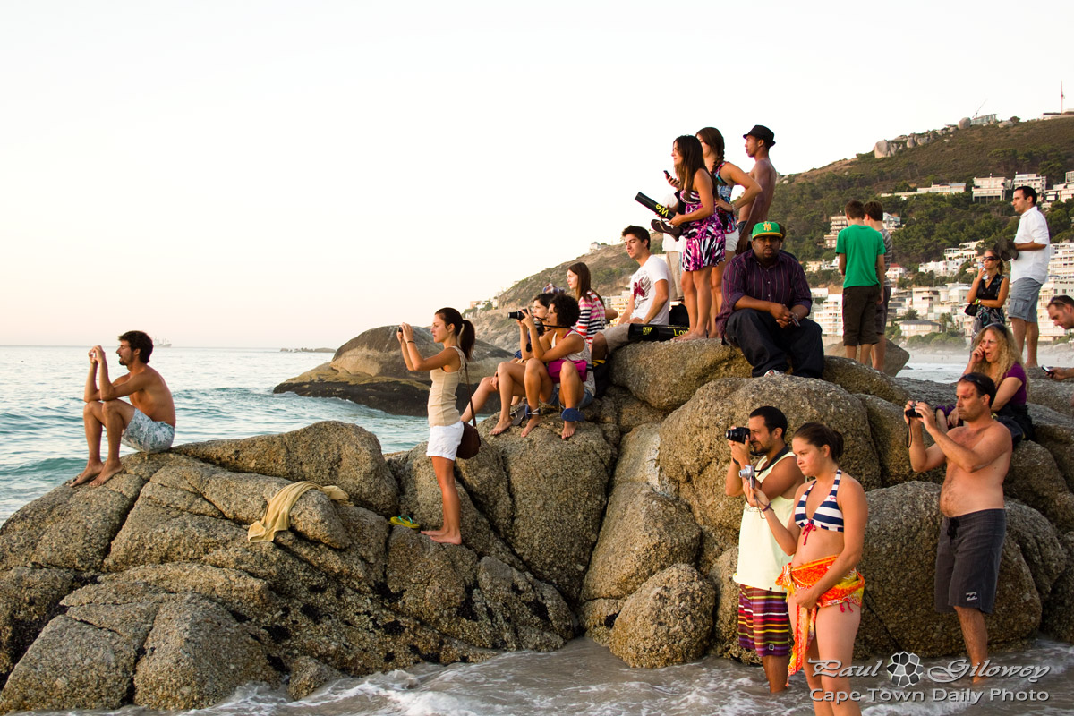 People sitting on a rock, taking a photo of the sunset