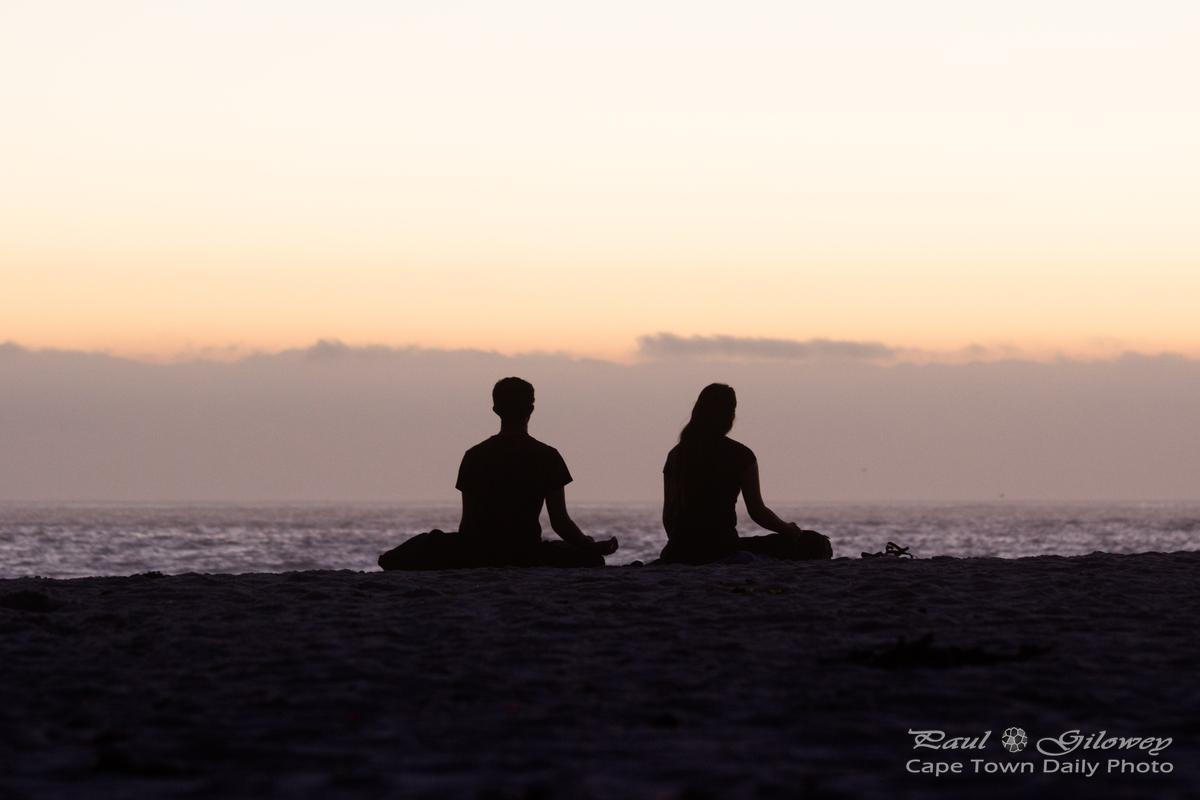Couple meditating on Camps Bay beach
